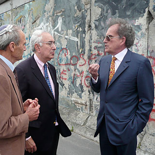 David Berlinski (r) discusses the implications of eugenics and evolution with Gerald Schroeder (l) and Ben Stein in front of the Berlin Wall.